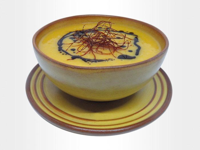 zdjelica s juhom od bundeve ukrašenom bučinim uljem i nitima od čilija