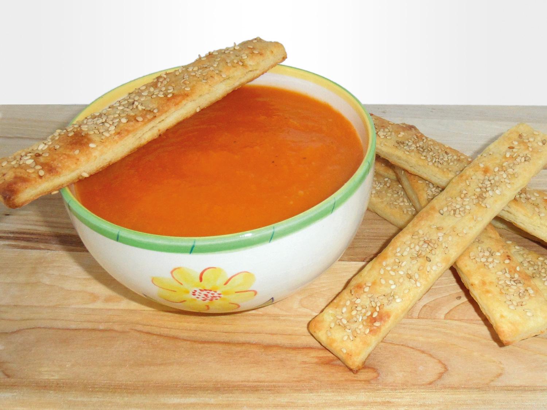 zdjelica s juhom od mrkve, pored nje štapići od kukuruznog tijesta